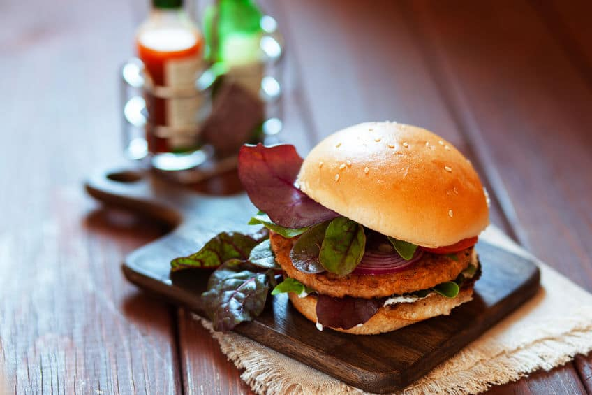 Fresh spicy grilled kosher hamburger on a rustic wooden table
